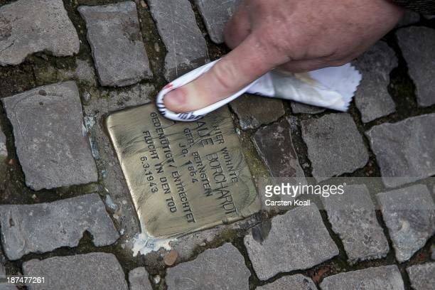 Man cleans so called Stolpersteine brass stumbling blocks to commemorate the 75th anniversary of the Kristallnacht pogroms on November 9 2013 in...