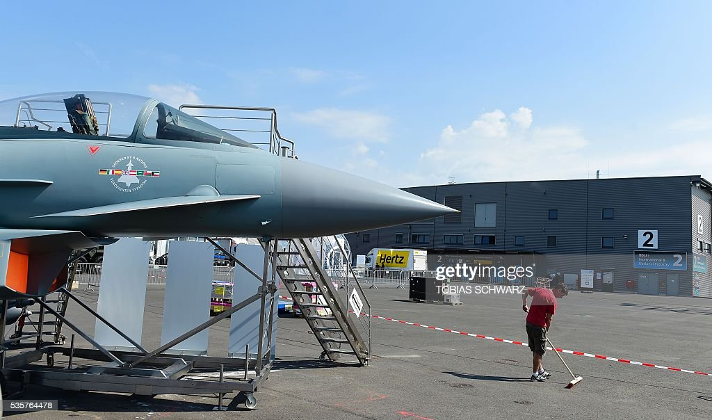 A man cleans the area around a 'Eurofighter Typhoon' aircraft on display at the International Aerospace Exhibition (ILA) in Schoenefeld on May 30, 2016. The Aerospace Exhibition at Schoenefeld Airport takes place from June 1 to 4, 2016. / AFP / TOBIAS