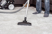 Closeup of the head of a modern vacuum cleaner used when vacuuming einens thick white carpet, in the background is a man.