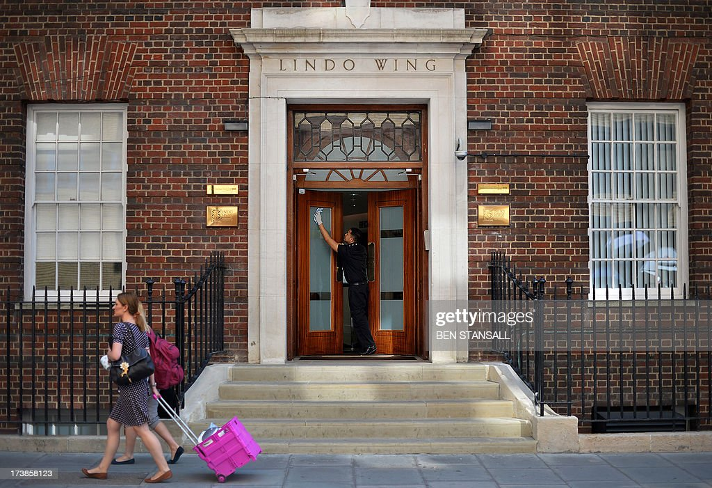 A man cleans the door at the Lindo Wing of St Mary's Hospital in London, on July 18, 2013, where Prince William and his wife Catherine's baby is expected to be born. The long wait for the birth of Britain's royal baby is record business for bookmakers, as punters worldwide bet on a girl called Alexandra to be born any day now.
