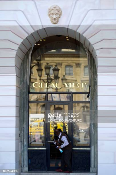 A man cleans the door of the Chaumet jewellery and watchmaking house on April 26 2013 at the Place Vendome in Paris AFP PHOTO / LIONEL BONAVENTURE