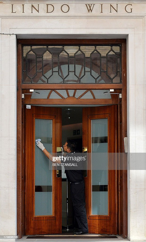 A man cleans the door of the Lindo Wing of St Mary's Hospital in London, on July 18, 2013, where Prince William and his wife Catherine's baby is expected to be born. The long wait for the birth of Britain's royal baby is record business for bookmakers, as punters worldwide bet on a girl called Alexandra to be born any day now. AFP PHOTO / BEN STANSALL