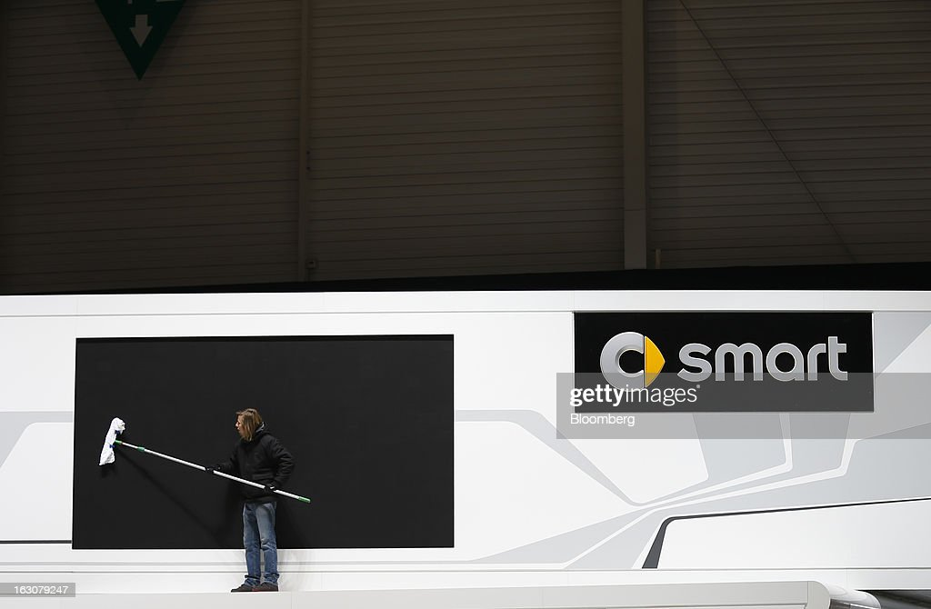 A man cleans the giant television screen above the Smart automobile stand ahead of the opening day of the 83rd Geneva International Motor Show in Geneva, Switzerland, on Monday, March 4, 2013. This year's show opens to the public on Mar. 7, and is set to feature more than 100 product premiers from the world's automobile manufacturers. Photographer: Valentin Flauraud/Bloomberg via Getty Images