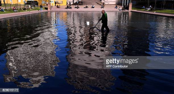 A man cleans the Lake of Reflections at the ANZAC memorial in Sydney's Hyde Park on August 9 2017 / AFP PHOTO / William WEST