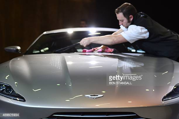 A man cleans the new Bond car an Aston Martin DB10 during an event to launch the 24th James Bond film 'Spectre' at Pinewood Studios at Iver Heath in...