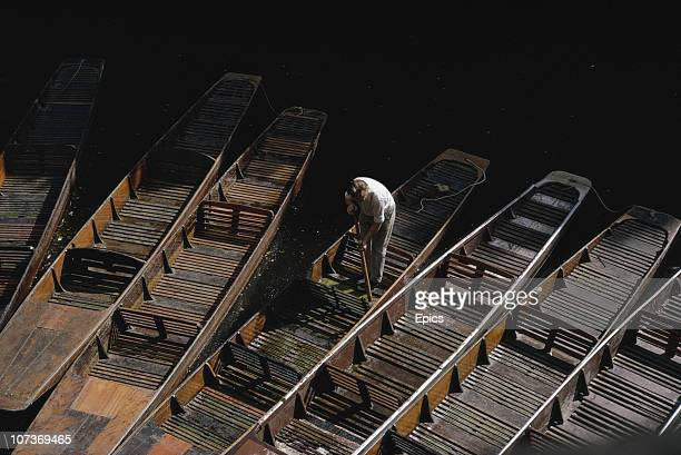 A man cleans the punts near Magdalene Bridge in time for students and tourists in the University town of Oxford July 1970
