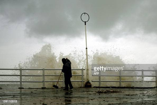 A man cleans the sidewalk next to the shore of the southern Lebanese city of Sidon on January 8 2013 Stormy weather including high winds and heavy...