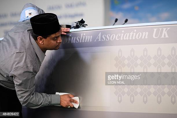 A man cleans the stage as members of the Ahmadiyya Muslim community prepare to listen to a speech by the fifth Caliph of the Ahmadiyya faith Mirza...