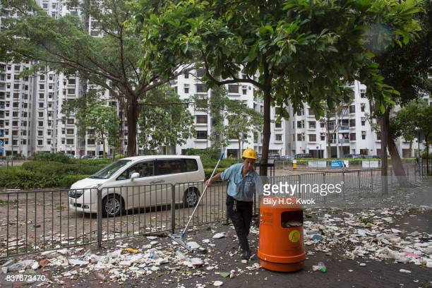 A man cleans the street as Typhoon Hato hits Hong Kong on August 23 2017 in Hong Kong Hong Kong Hong Kong's weather authorities raised Typhoon Hato...