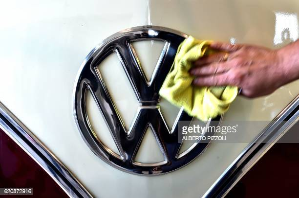 A man cleans the VW logo on a vintage Volkswagen Kombi bus restored by the 'T1 specialist' team on November 3 2016 at the garage Nucci in Florence...