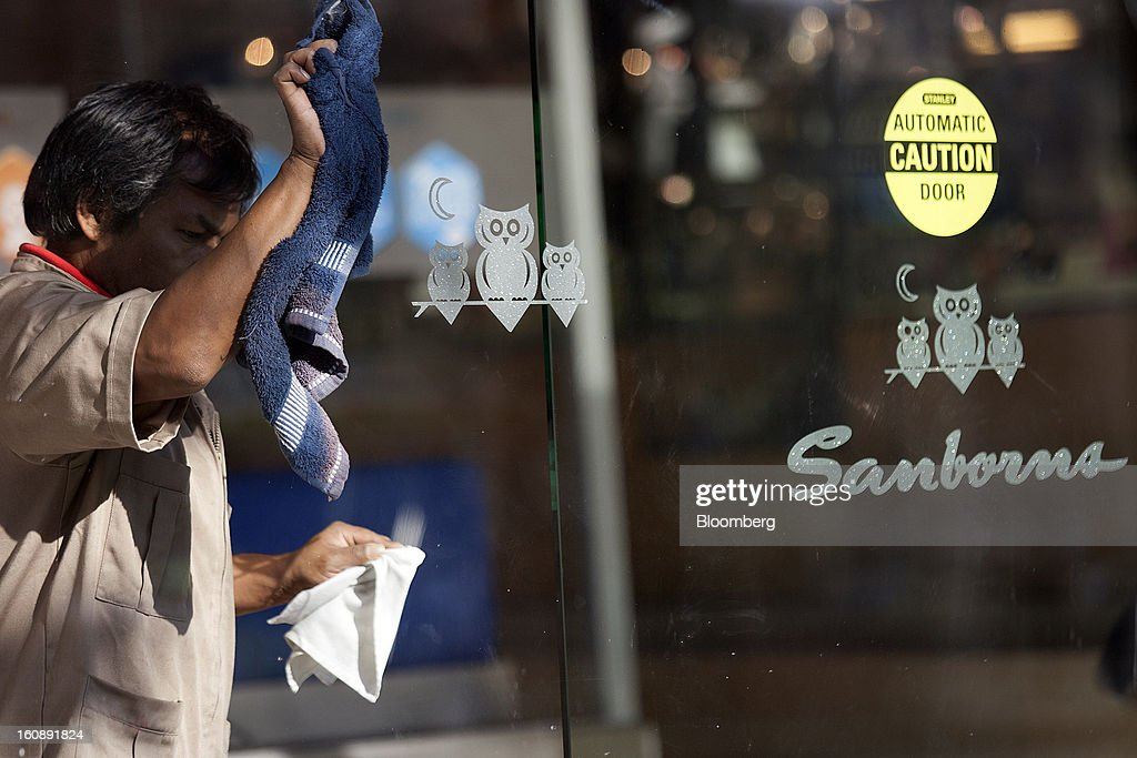 A man cleans the window of a Sanborns Grupo SAB store in Mexico City, Mexico, on Thursday, Feb. 7, 2013. Billionaire Carlos Slim is taking Mexican retailer Grupo Sanborns SAB public as revenue surges from sales to consumers looking to shop at its Saks Fifth Avenue stores and buy Apple Inc. iPads. Photographer: Susana Gonzalez/Bloomberg via Getty Images