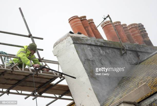 A man cleans tiles on a roof of a building besides the beach at Weymouth as the resort prepares for the start of the holiday season on April 3 2017...