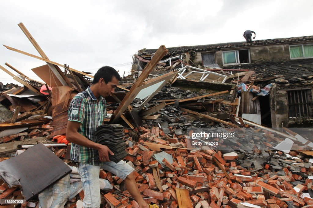 A man cleans up debris at a destroyed home after typhoon Fitow made landfall on October 8, 2013 in Wenzhou, China. At least ten people were killed and five others missing after typhoon Fitow made landfall in Fujian province on Monday morning.