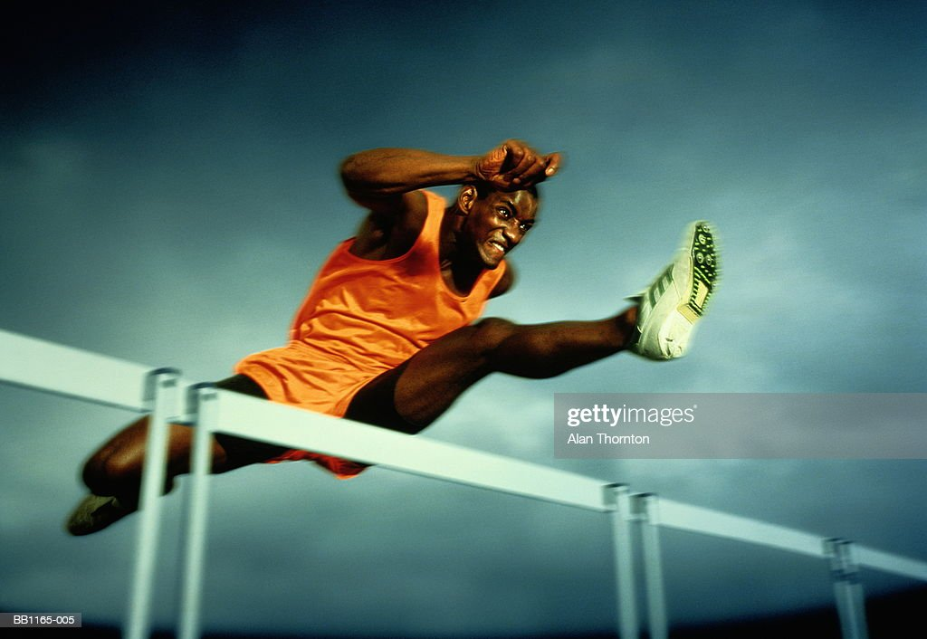 Man clearing hurdle, against grey sky (Digital Enhancement) : Stock Photo