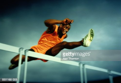 Man clearing hurdle, against grey sky (Digital Enhancement) : Stock Photo