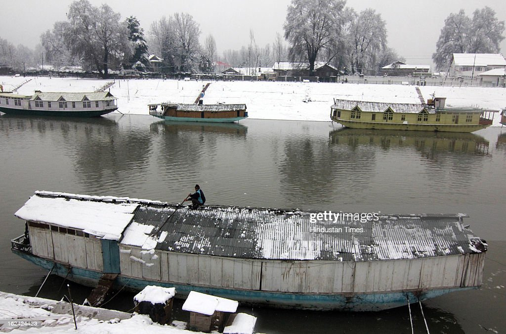 A man clearing snow from his roof top on his house boat during fresh Snowfall on February 23, 2013 in Srinagar, India. The Jammu-Srinagar National Highway remained closed for the second day on Saturday even as fresh snowfall across Kashmir prompted authorities to issue an avalanche warning in higher reaches of the Valley.