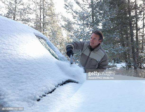 Man clearing snow off car