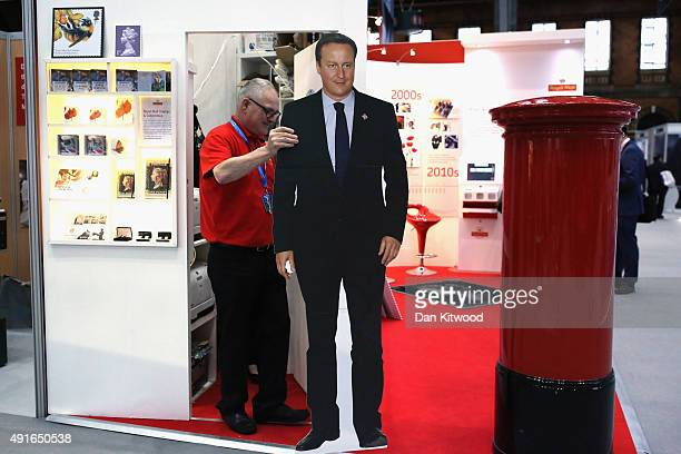 A man clears a cardboard cutout of British Prime Minister David Cameron from a Royal Mail stand after the Prime Minister's keynote speech to...