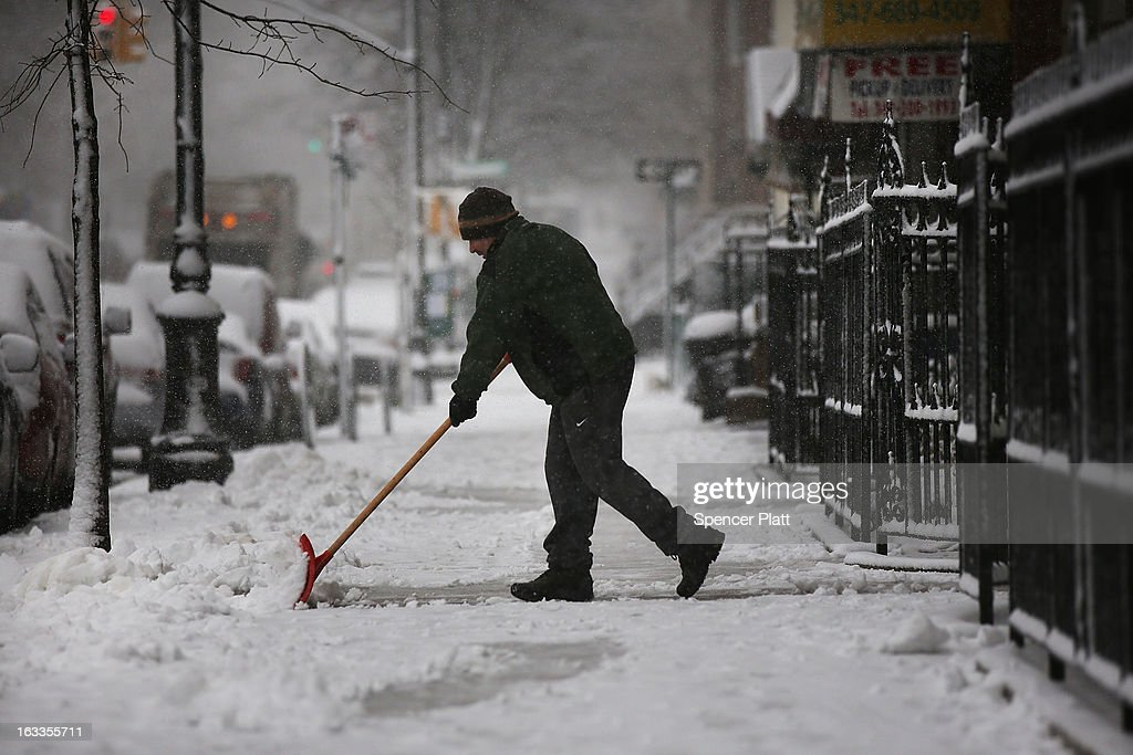 A man clears a sidewalk of snow on March 8, 2013 in the Brooklyn borough of New York City. As a week-old storm slowly moves out to sea, the New York City area is expecting 1 to 3 inches of snow with more in areas north and west of the city. The storm has caused flight delays at area airports and numerous schools have delayed start times.