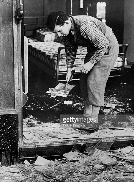 A man clears away the broken glass from the Jewish Kaliski Bedding Establishment The previous night known as Kristallnacht a German mob murdered...