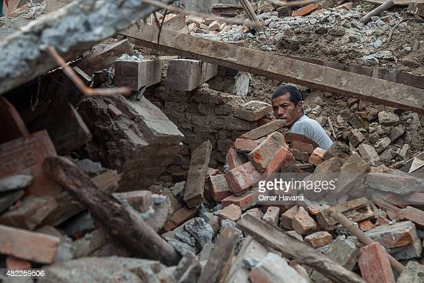 A man clears debris from a collapsed home on July 29 2015 in Bhaktapur Nepal Three months after the earthquake that hit Nepal on April 25th and with...