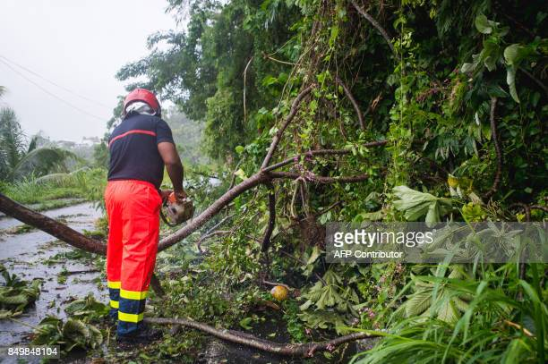 A man clears debris from a street in SaintPierre on the French Caribbean island of Martinique after it was hit by Hurricane Maria on September 19...