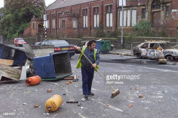 A man clears debris from a street June 21 2001 in north Belfast Northern Ireland Almost 40 officers were injured when fierce fighting broke out...