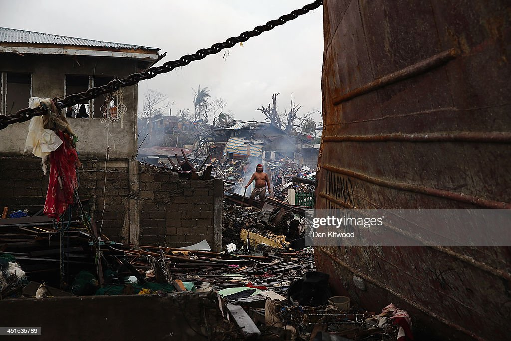 A man clears debris from in front of his home (left) near the shoreline where several tankers ran aground on November 23, 2013 in Leyte, Philippines. Bodies continue to be recovered nearly two weeks after the devastating Typhoon Haiyan as the official death toll now exceeds 5,000. The typhoon, which ripped through the Philippines over a week ago, has been described as one of the most powerful typhoons ever to hit land, leaving thousands dead and hundreds of thousands homeless. Countries all over the world have pledged relief aid to help support those affected by the typhoon, but damage to the airport and roads have made moving the aid into the most affected areas very difficult. With dead bodies left out in the open air and very limited food, water and shelter, health concerns are growing.