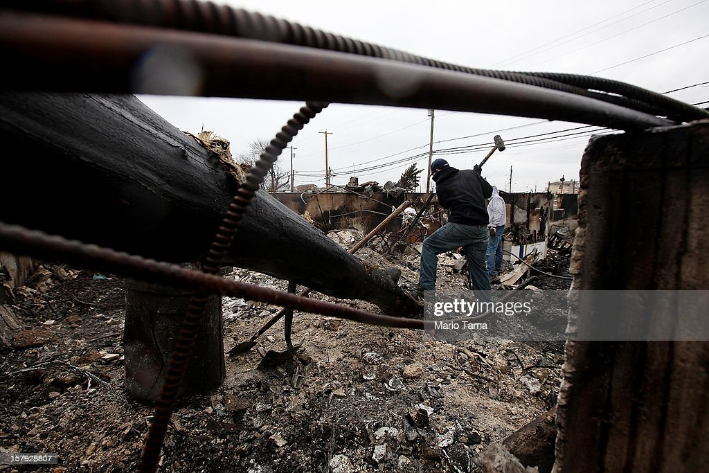 A man clears debris from the charred remains of a destroyed home in the hard hit Breezy Point neighborhood on December 7, 2012 in the Queens borough of New York City. Breezy Point, home to many New York City firefighters and police, lost 111 homes in a fast moving fire during Superstorm Sandy with many more homes severely damaged from flooding.