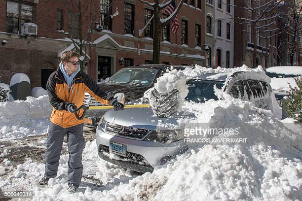 A man clears his car with a shovel near Central Park on January 24 2016 in New York A massive blizzard that claimed at least 16 lives in the eastern...