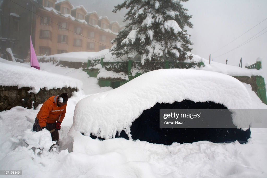 A man clears snow from a road next to a vehicle covered with snow during the season's first snowfall, on November 29, 2012 in Gulmarg, 54 km (35 miles) to the west of Srinagar, the summer capital of Indian-administered Kashmir, India. As the Kashmir valley received heavy snowfall in its upper reaches, the 434-km Srinagar-Leh National highway, the highest motorable road in the world, was closed to traffic. The famous ski resort of Gulmarg also experienced the first heavy snowfall of the season, officials said. Gulmarg, located less than six miles from the ceasefire line or Line of Control (LoC) that divides Kashmir between India and Pakistan, is known for long-run skiing, snow-boarding, heli-skiing and steep mountains.