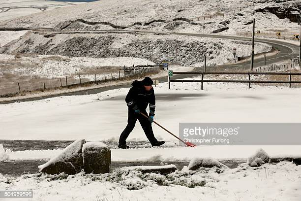 A man clears snow from his driveway in the Peak District near Buxton on January 14 2016 in Buxton England Overnight snowfall on the high ground of...
