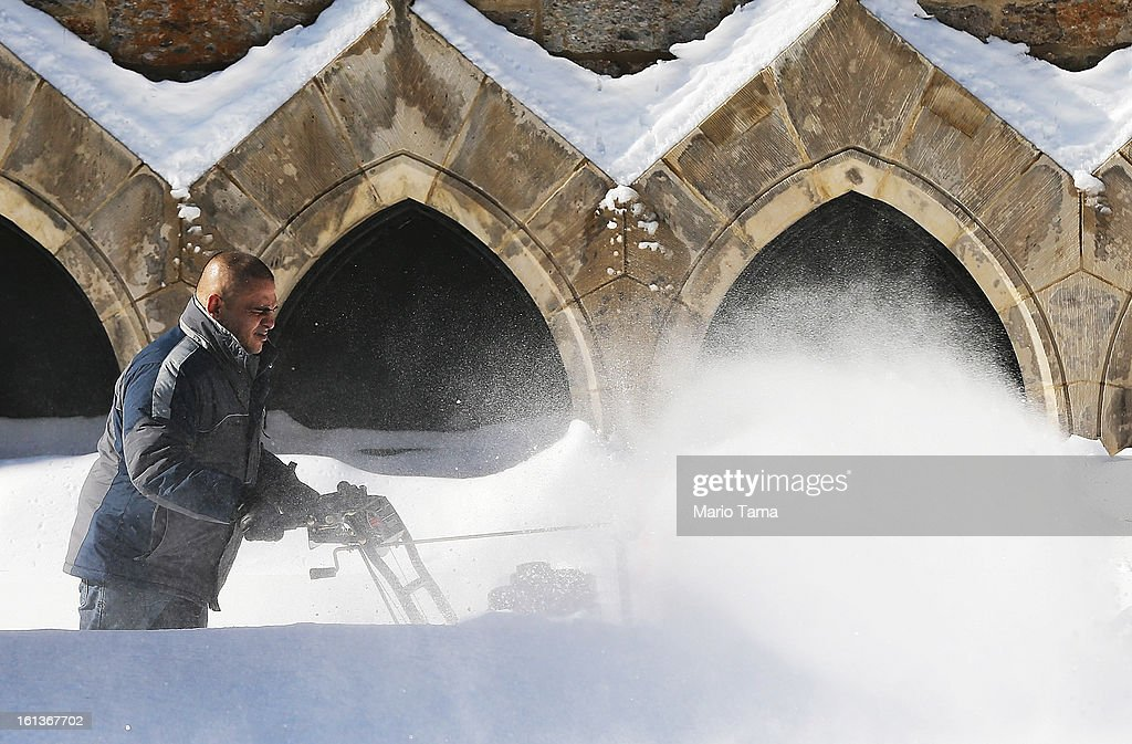 A man clears snow in front of a church in the Back Bay neighborhood following a powerful blizzard on February 10, 2013 in Boston, Massachusetts. The storm dumped more than two feet of snow in parts of New England and more than 200,000 Massachusetts customers remain without power.