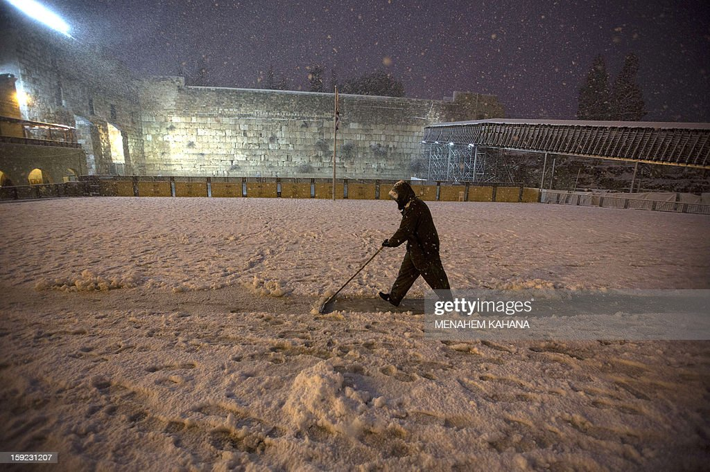A man clears snow near the Western Wall in the old city of Jerusalem on January 10, 2013. Jerusalem was transformed into a winter wonderland after heavy overnight snowfall turned the Holy City and much of the region white, bringing hordes of excited children onto the streets.