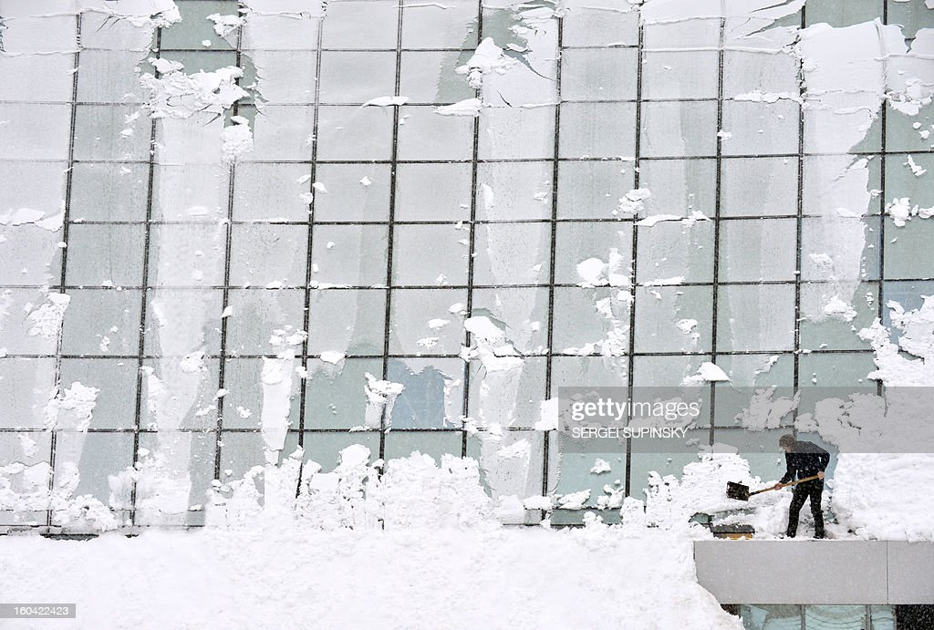 A man clears snow on January 31, 2013 on the canopy roof above a shopping mall entrance after heavy snowfall in central Kiev, Ukraine.