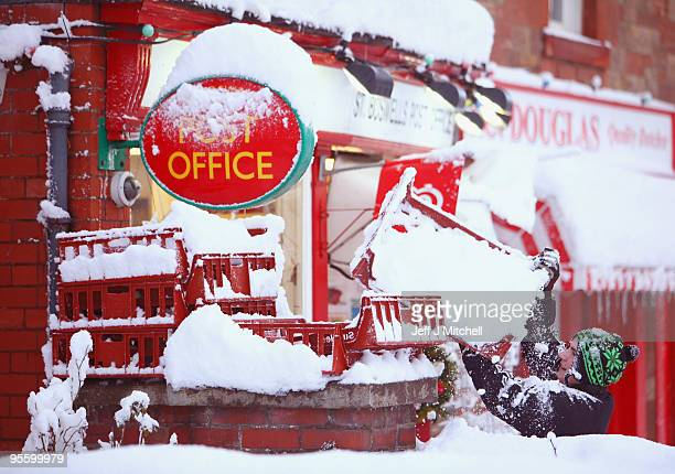 A man clears snow the Post Office in Scottish Borders village of St Boswells on January 6 2009 in St Boswells Scotland Extreme weather warnings have...