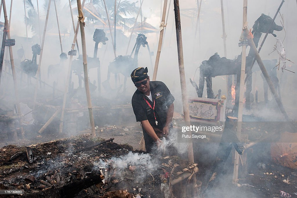 A man clears the debris of a burned sarchophagus at the cremation site during a Balinese Hindu mass cremation on August 18, 2013 in Ubud, Bali, Indonesia. More than 60 corpses were collectively cremated to share the expense of the ceremony. Well known as Ngaben, it is one of the most important ceremonies for Balinese Hindu people, as they believe it will free the spirit from the deceased body so it can reincarnate.