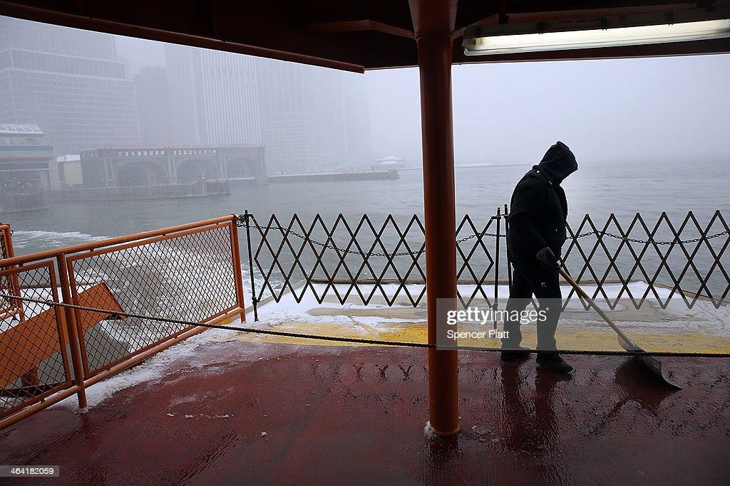 A man clears the deck of the Staten Island Ferry of snow and ice during a snowstorm that is moving through the Northeast on January 21, 2014 in New York City. Along with dropping arctic tempertures the storm is expected to bring three to five inches by nightfall, with another four to six inches falling overnight.