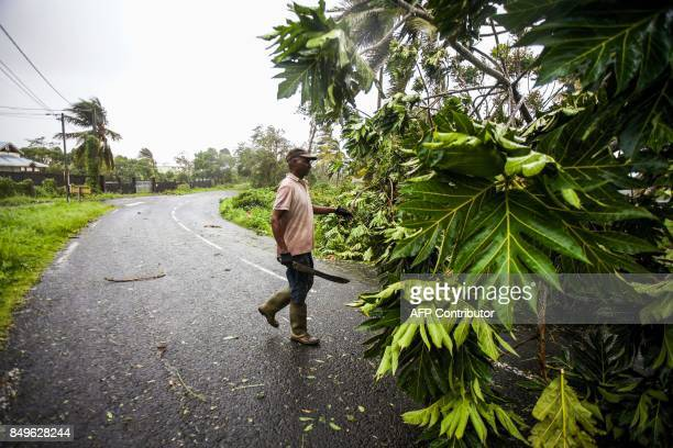 A man clears the road from fallen tree branches in the village of Viard Petit Bourg on September 19 2017 in the French territory of Guadeloupe after...