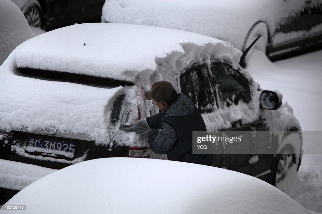 A man clears the snow from his car on February 19, 2013 in Nanjing, China. Heavy snow hit large areas of east China on Tuesday.