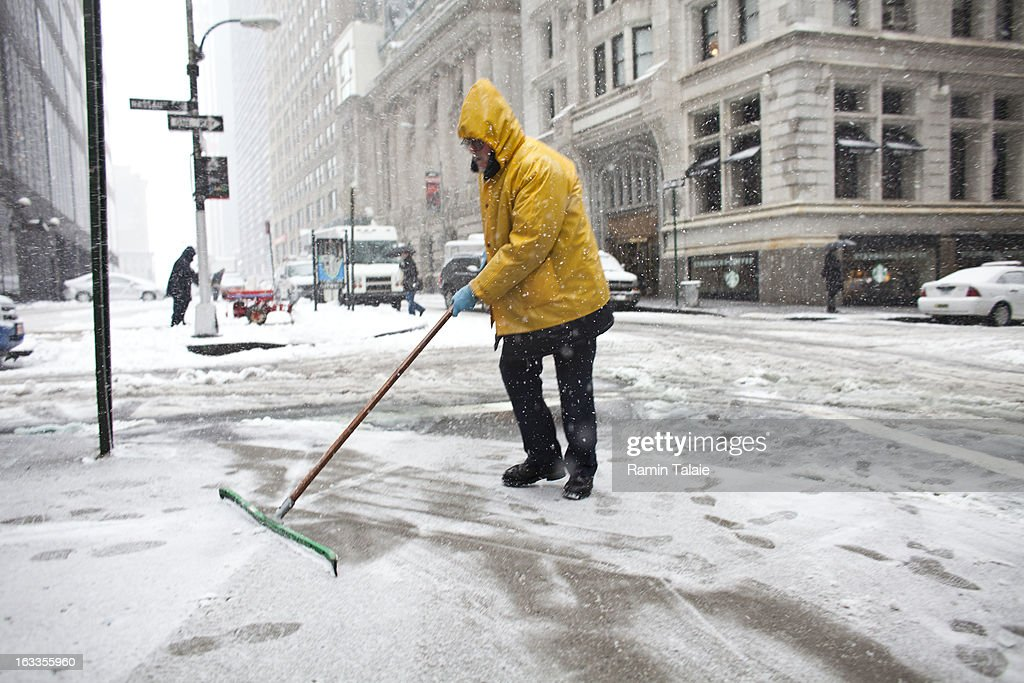 A man clearsthe sidewalk on March 8, 2012 in New York City. The storm part of the same system that pummeled the Midwest is expected to dump one to two inches of snow in the New York Metro area.
