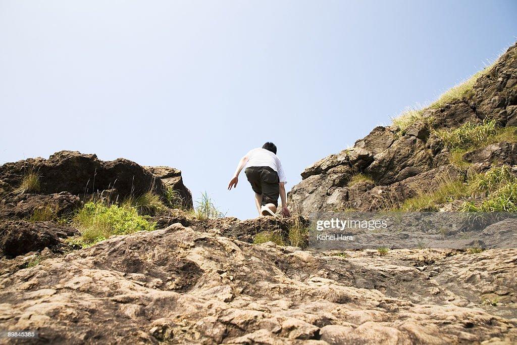 man climbing a cliff : Stock Photo