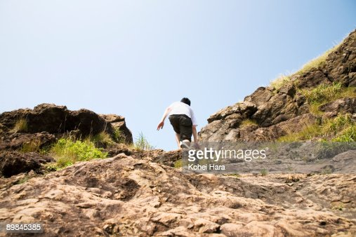 man climbing a cliff : Stock Photo