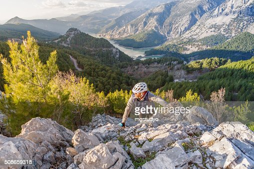 Man climbing alone at the dawn in a forest : Stock Photo