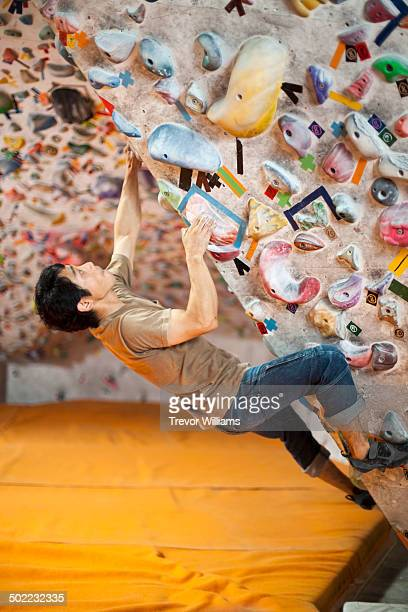 A man climbing at a bouldering gym