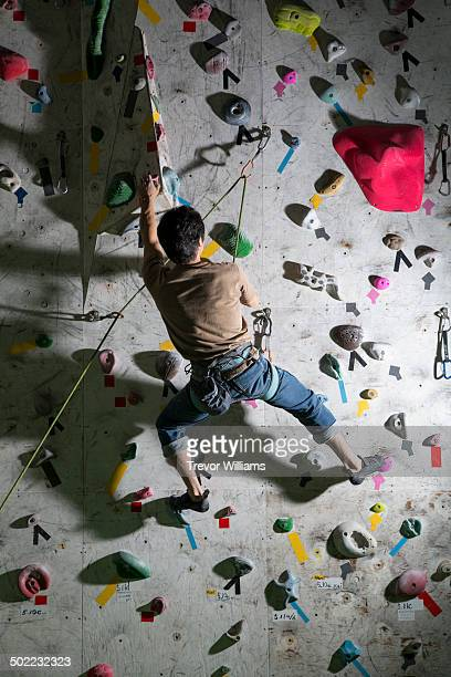 A man climbing at a rock climbing gym