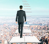 Businessman climbing abstract open book ladder on city background. Success and education concept
