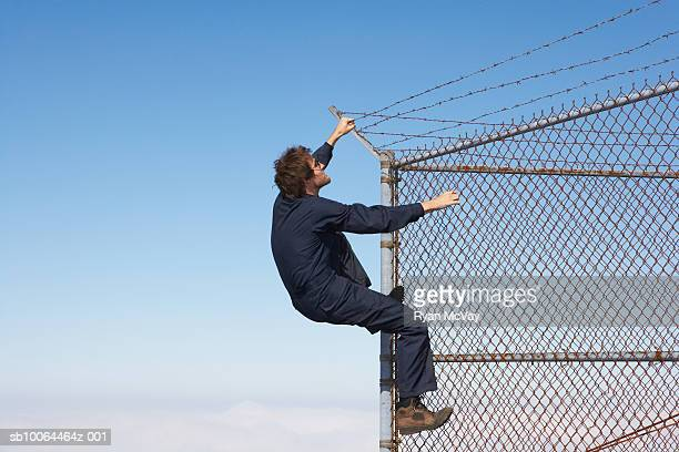 Man climbing chain link fence with barbed wire on top