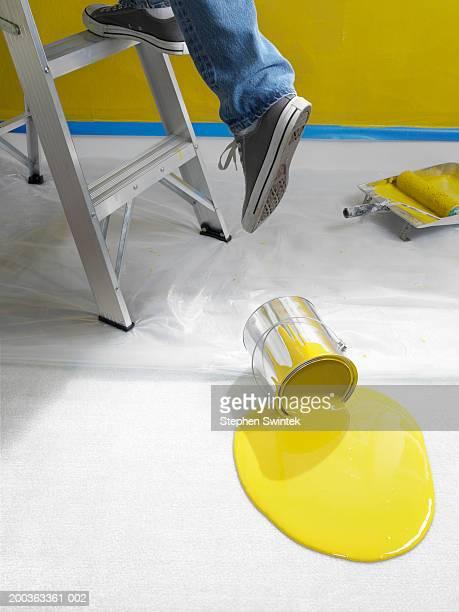 Man climbing ladder, spilled paint on floor