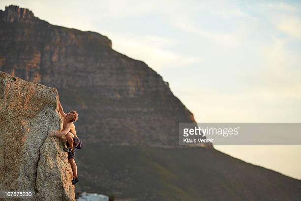 Man climbing on rock side at sunset